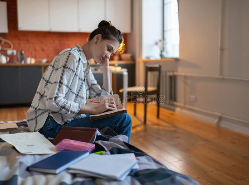 Teenager writing notes sitting on bed. Beautiful concentrated teenage female student writing notes preparing for exam while sitting on bed royalty free stock images