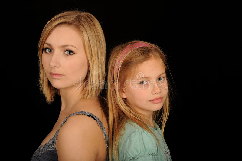 Teenager and young sister. Portrait of teenager standing back to back with younger sister, black background stock photos