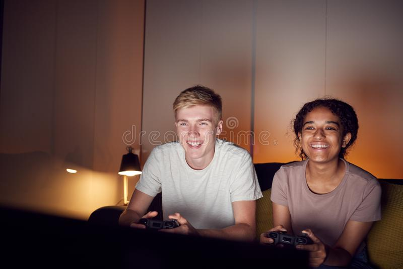 Teenagerpaar sitzen auf Sofa zu Hause am Computer spielen zusammen lizenzfreie stockfotografie