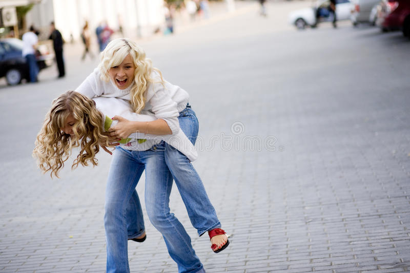 Teenagers. Two teenage girls playing in city stock images