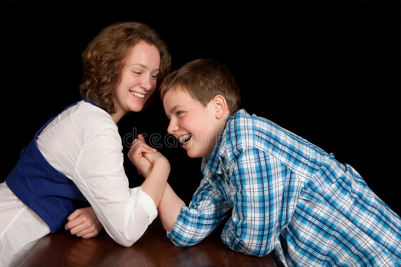Teenagers arm-wrestling. Caucasian teenager boy and girl enjoying an arm-wrestling challenge royalty free stock images