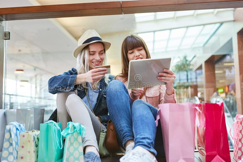 Teenagers as consumers shopping online. Two teenagers as consumers shopping online at the mall royalty free stock photography