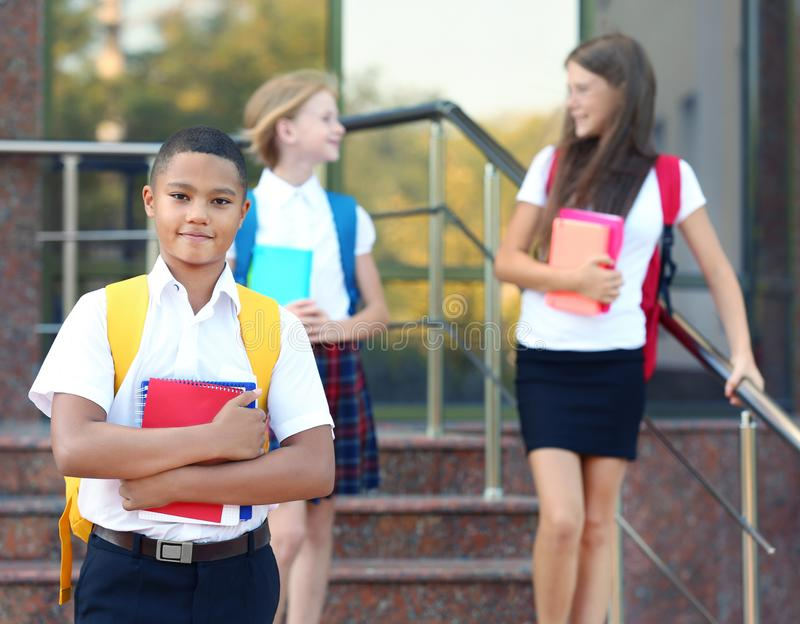 Teenagers with backpacks and notebooks standing on school stairs. Cheerful teenagers with backpacks and notebooks standing on school stairs royalty free stock image