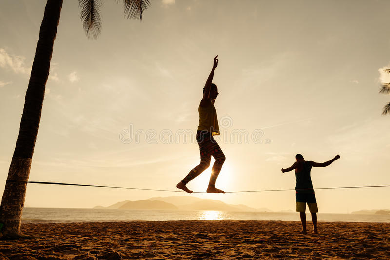 Teenagers balance on slackline silhouette royalty free stock image