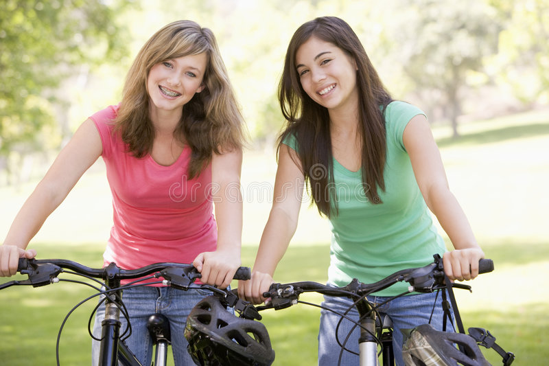 Teenagers On Bicycles. Smiling At Camera royalty free stock photography