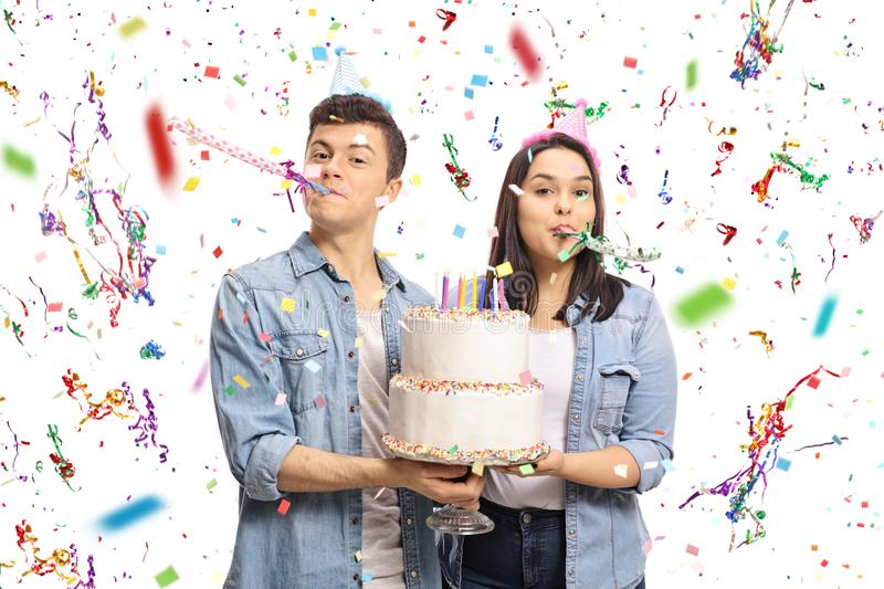 Teenagers with a birthday cake and party horns stock photography
