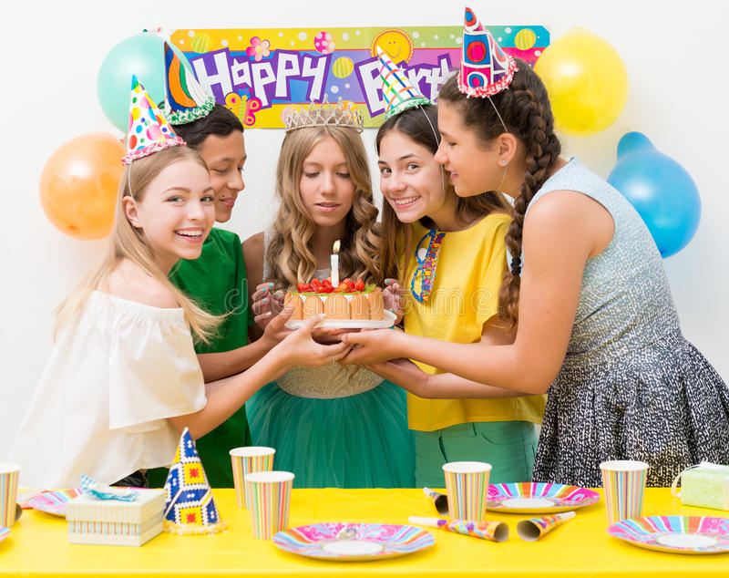 Teenagers at a birthday party. Girl blows out the candle on the cake with a group of teenagers at a birthday party stock image