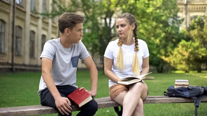 Teenagers bored with studies having conversation, exhausted from reading books. Stock photo stock photo