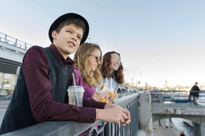 Teenagers boy and two girls with street food talking outdoor stock photography