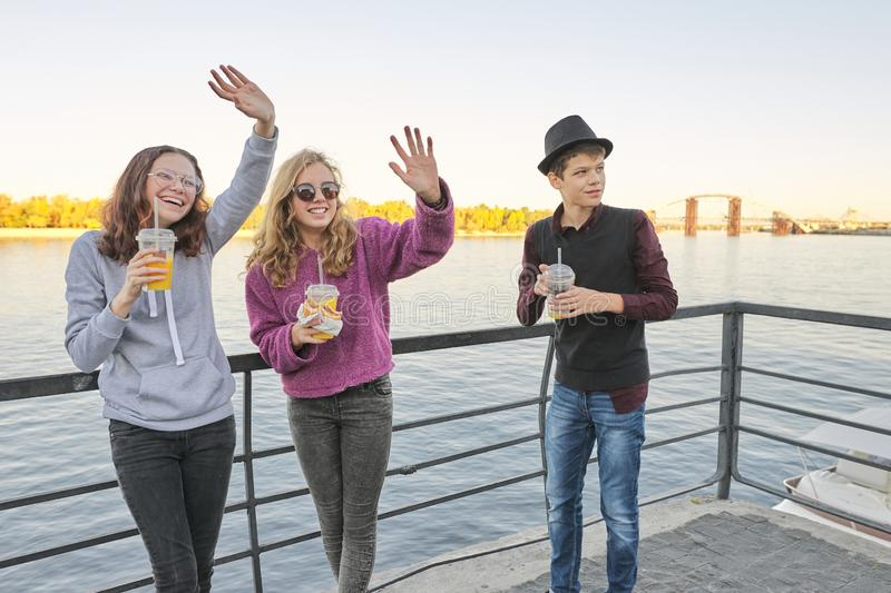 Teenagers boy and two girls with street food talking outdoor.  royalty free stock photo