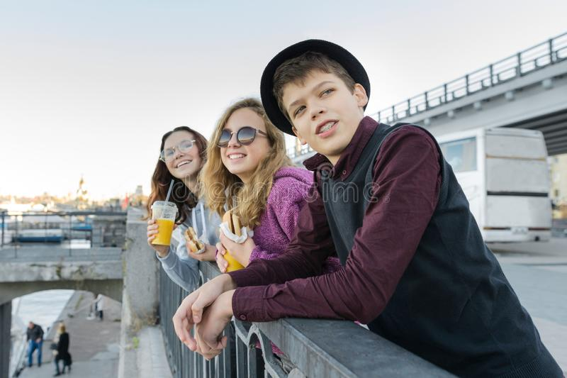 Teenagers boy and two girls with street food talking outdoor royalty free stock photos