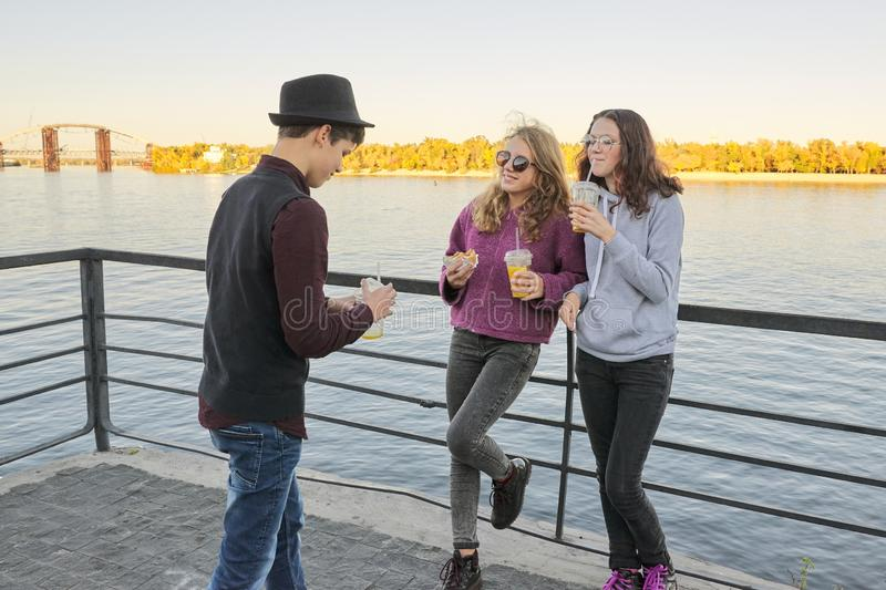 Teenagers boy and two girls with street food talking outdoor.  stock image