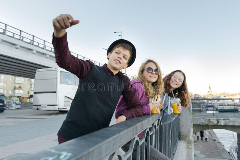 Teenagers boy and two girls with street food talking outdoor stock photo
