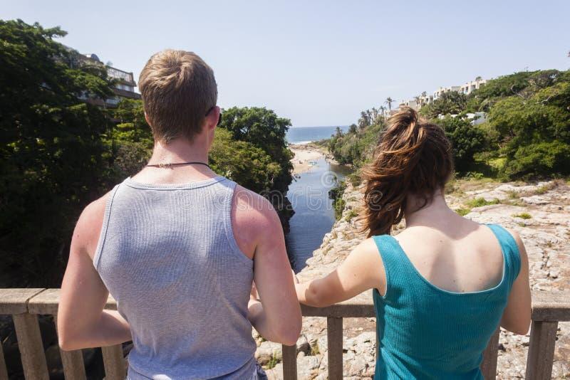 Teenagers Bridge Lagoon Beach. Teenagers boy girl on bridge overlooking lagoon beach ocean landscape stock image