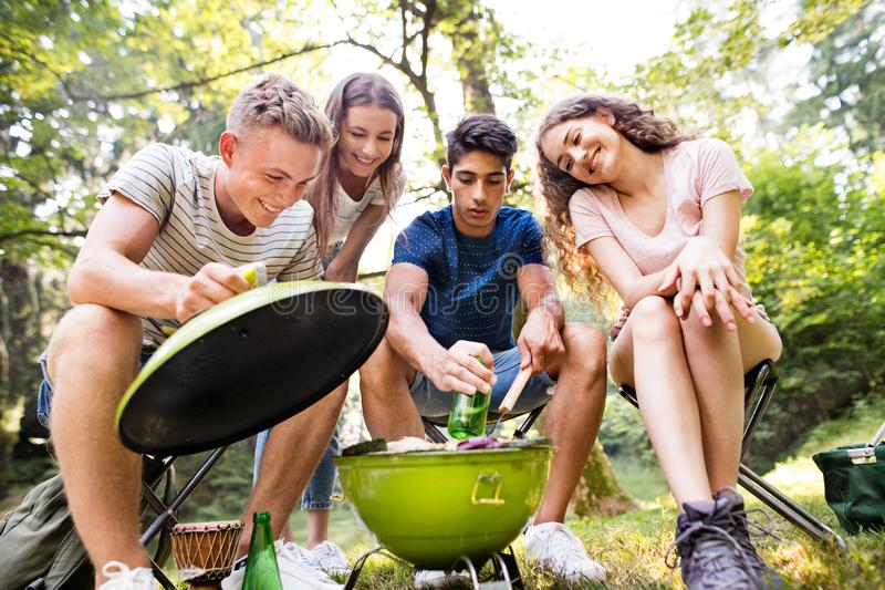 Teenagers camping, cooking meat on barbecue grill. Beautiful teenagers enjoying camping vacations in forest, cooking meat on barbecue grill royalty free stock images