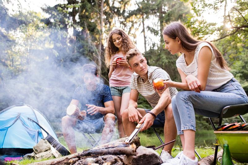 Teenagers camping, cooking meat on bonfire. royalty free stock image