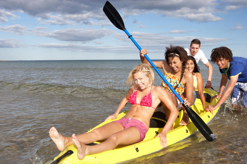 Teenagers in canoe in the sea royalty free stock images