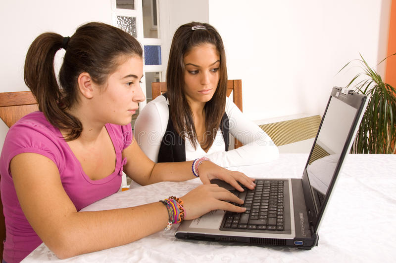 Teenagers with computer. Two young teenagers while handling a computer for fun, study or etc stock images