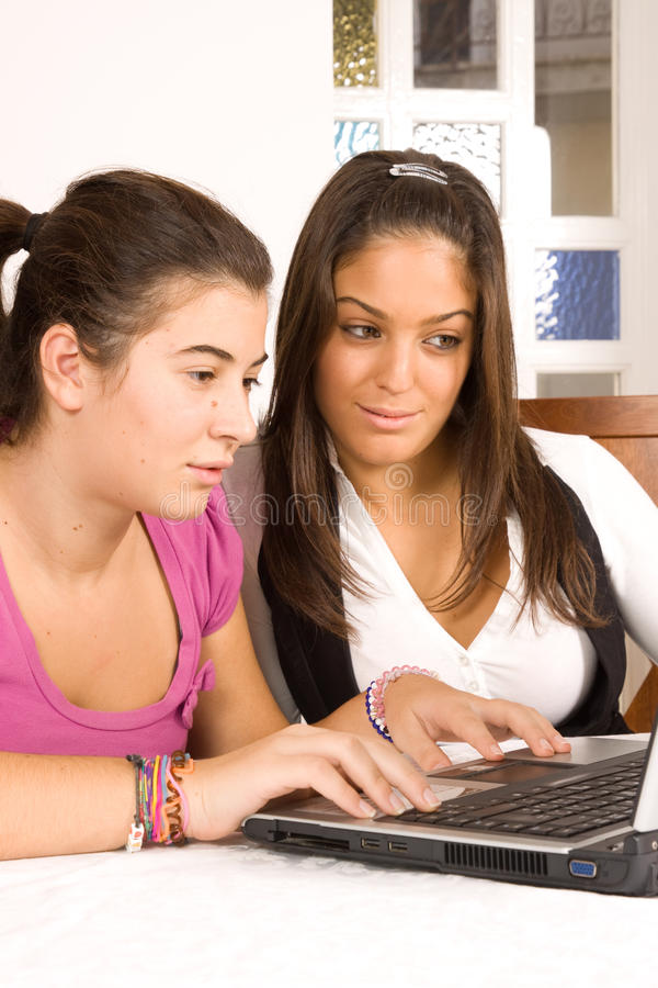 Teenagers with computer. Two young teenagers while handling a computer for fun, study or etc stock photos
