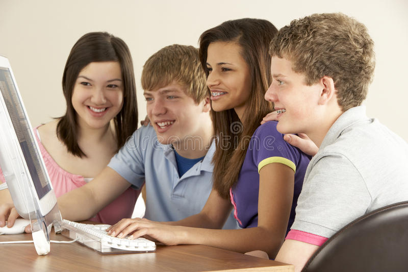 Teenagers on Computer at Home. Smiling royalty free stock photo