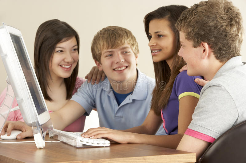 Teenagers on Computer at Home. Looking Happy royalty free stock image