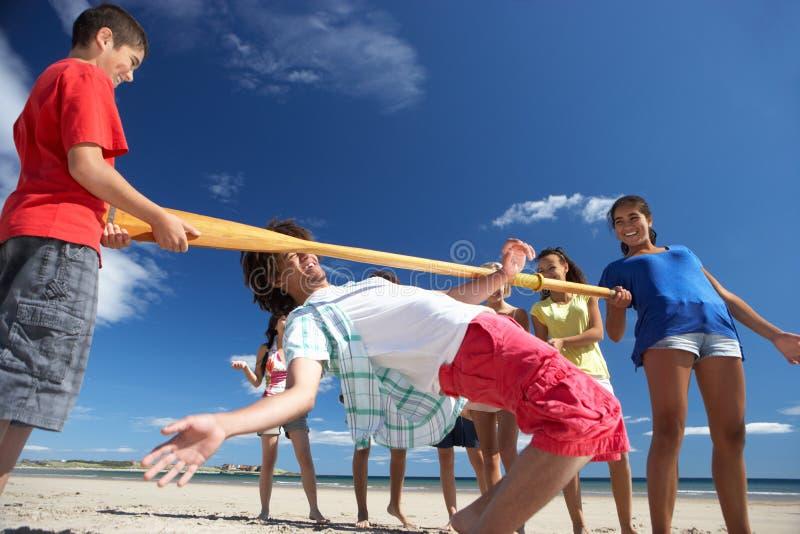 Teenagers doing limbo dance on beach stock image