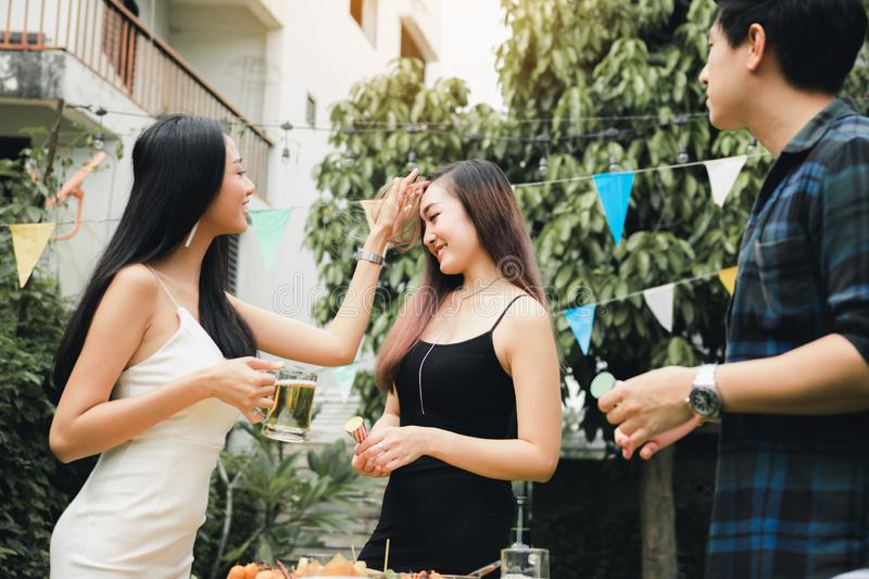Teenagers are enjoying a garden party at home and holding the beer glass in hand royalty free stock images