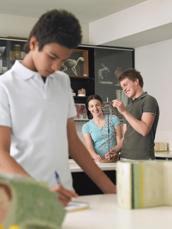 Teenagers Examining DNA Model. In science class royalty free stock photography