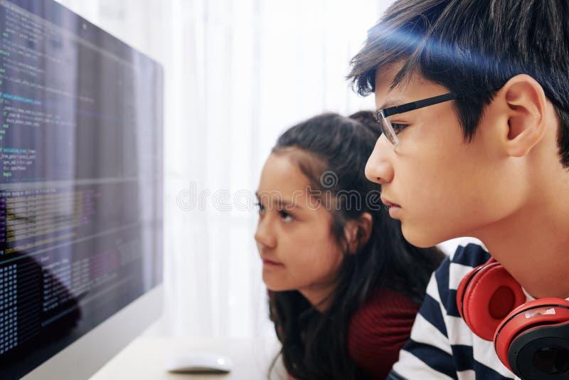 Teenagers examining programming code computer screen. Serious pensive teenagers examining programming code on screen of computer and searching for mictake royalty free stock images