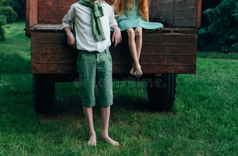 Teenagers on the farm, farmer`s children in the summer. harvesting and rest. a barefooted girl in a green dress is sitting in an. Old caravan, and beside her stock photos