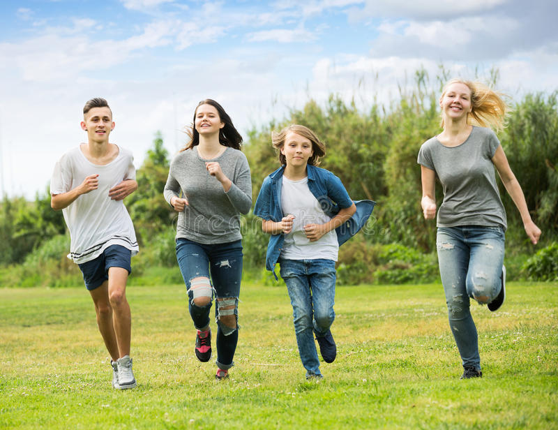 Teenagers friends running on meadow stock images