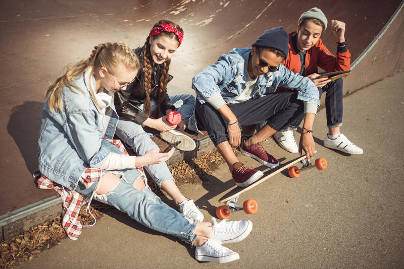 Teenagers group sitting sitting together and using digital devices. At skateboard park stock photography