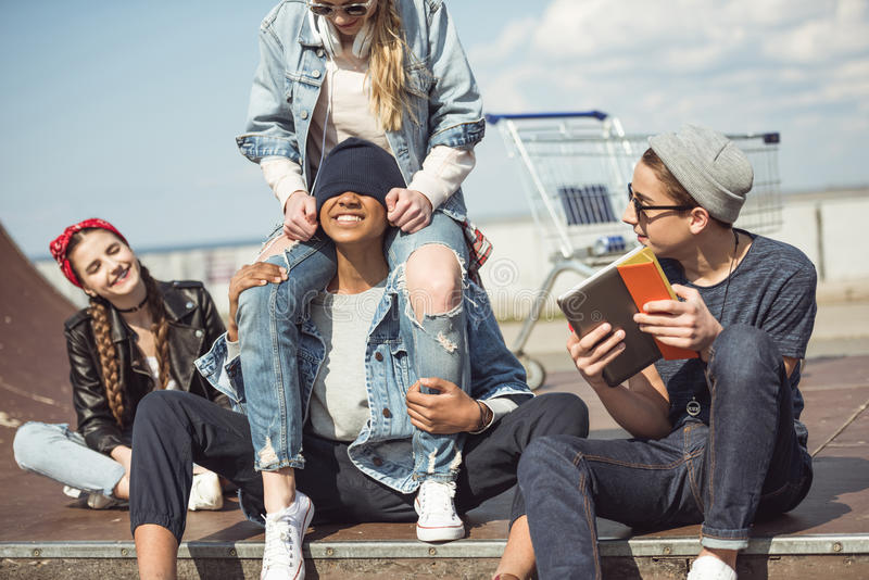 Teenagers group sitting together on the ramp and having fun. At skateboard park stock photo