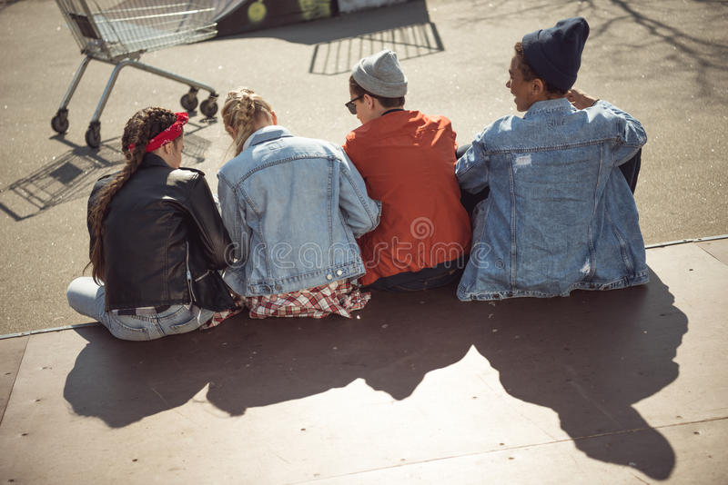 Teenagers group sitting together and talking at skatepark. Back view of teenagers group sitting together and talking at skatepark stock photography