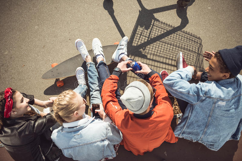 Teenagers group sitting together and talking at skatepark. Overhead view of teenagers group sitting together and talking at skatepark stock photography