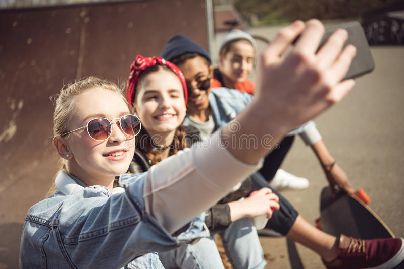 Teenagers group taking hipster selfie while sitting together at skateboard park. Smiling teenagers group taking hipster selfie while sitting together at royalty free stock photography