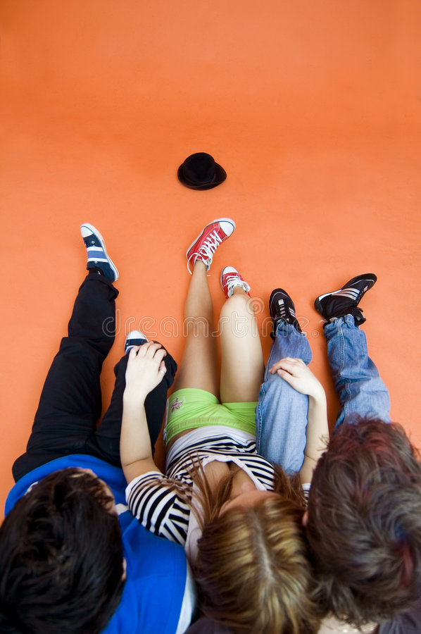 Teenagers and Hat. Three teenagers sitting together on floor, hat in front of them stock photography
