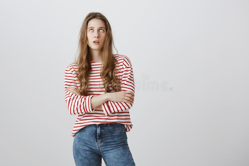 Teenagers hate when parents scolding. Bothered and annoyed european female student rolling eyes and sighing, standing. With crossed arms over gray background royalty free stock photography