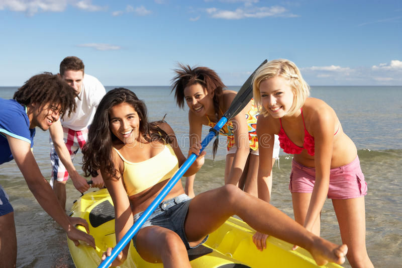 Teenagers having fun with a canoe stock photography