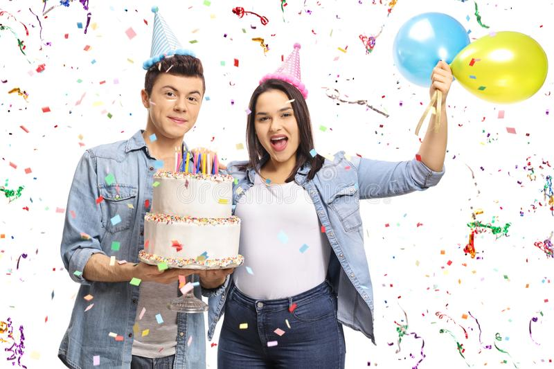 Teenagers holding a birthday cake and balloons with confetti streamers flying around them royalty free stock photos