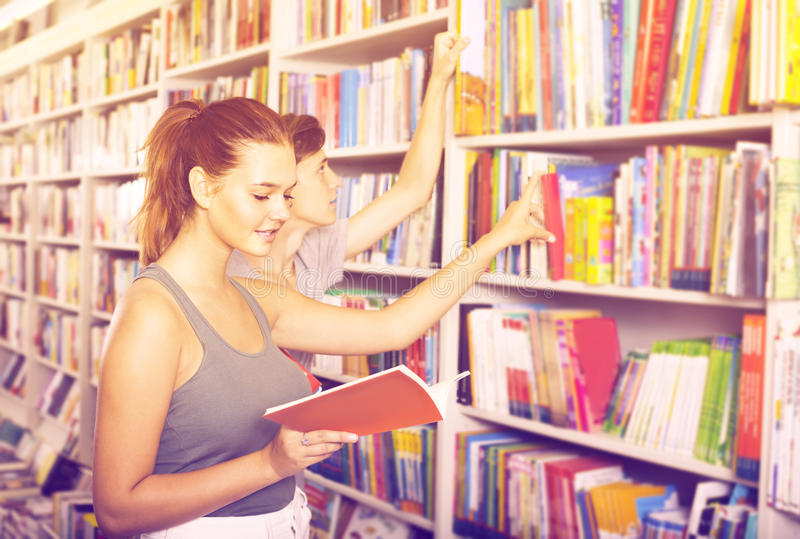 Teenagers holding book and reading new literature stock photo