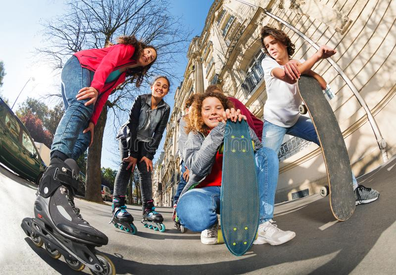 Teenagers with inline skates and skateboards stock images