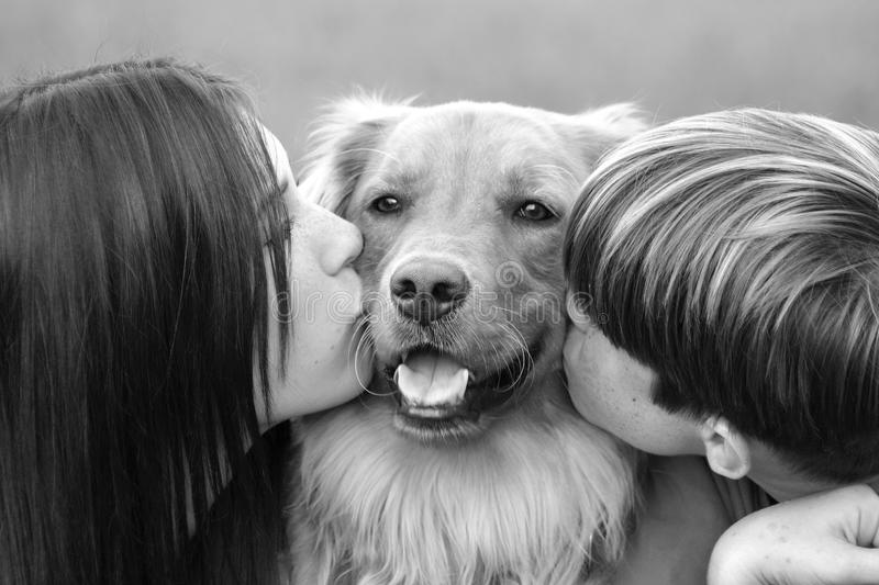 Teenagers Kissing Dog. Two Teenagers Kids Kissing Dog royalty free stock photo
