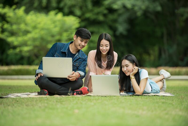 Teenagers with laptops on grass stock photos