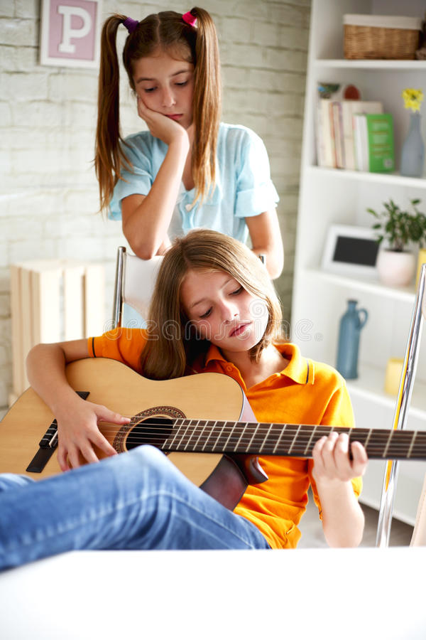 Teenagers learn to play guitar royalty free stock images