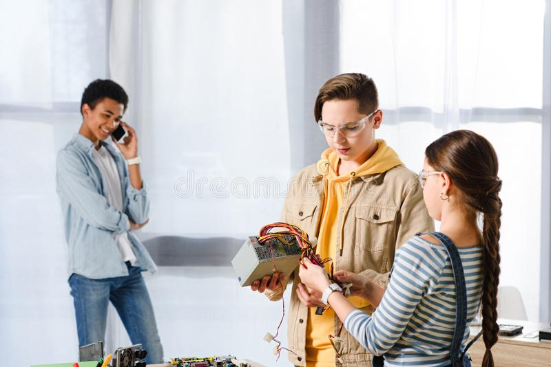 Teenagers looking at computer power supply. At home royalty free stock photo