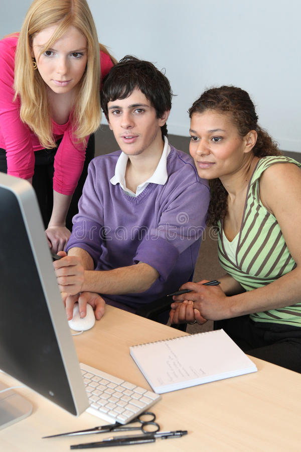 Teenagers looking at a computer. Screen stock image