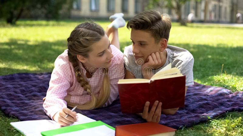 Teenagers looking at each other instead of learning, feeling desire to kiss royalty free stock photography
