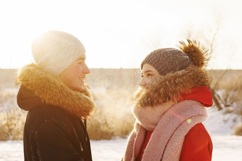 Teenagers in love. Date in winter. Adolescents in love on a date in winter. Boyfriend and girlfriend are looking at each other. Joy of being together. First love stock images
