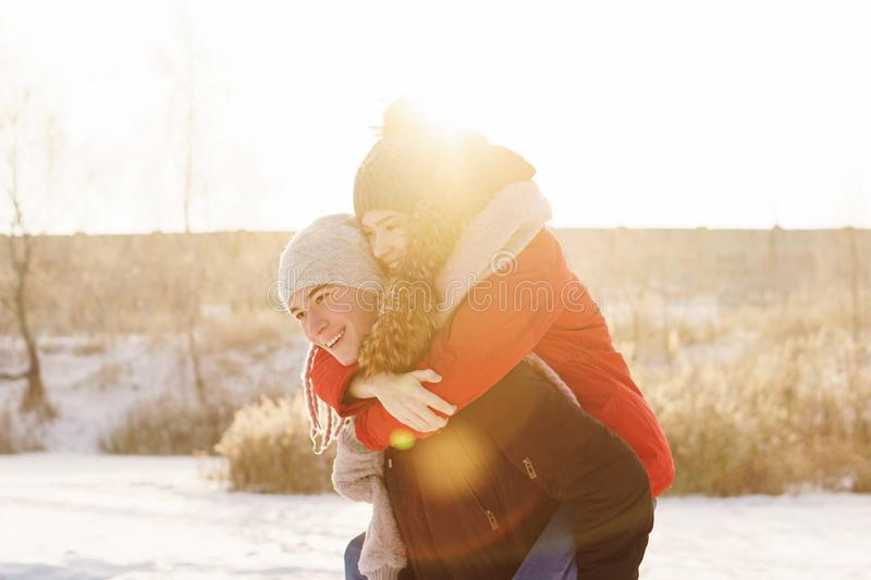 Teenagers in love. Date in winter. Adolescents in love on date in winter. Guy has his girlfriend piggyback. Joy of being together. First love. Concept for stock photos